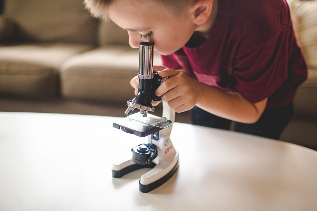 young-boy-looking-through-microscope-symbolizing-scientific-aspect-of-user-experience