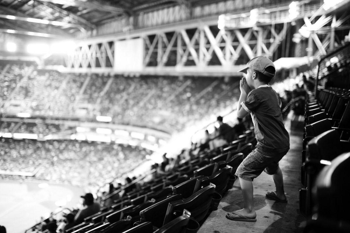 Kleiner Junge ist mit Leidenschaft am Anfeuern auf der Tribüne des Stadions. Sinnhaftes Bild für unsere Leidenschaft zum Inbound Marketing.